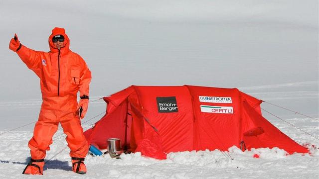 Thomas Ulrich auf einem Gletscher in rotem Genzkörperanzug, neben rotem Zelt.