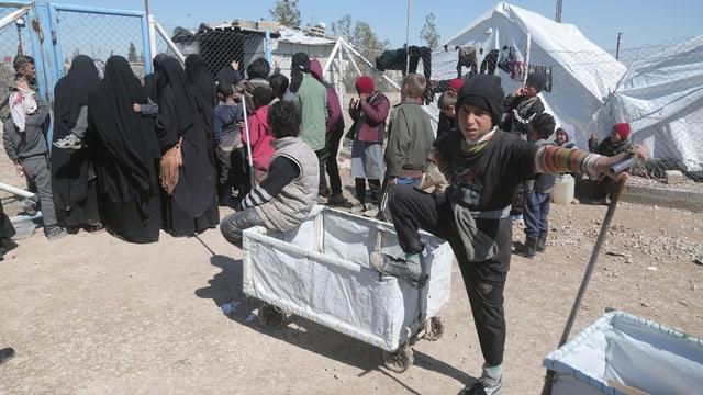 Frauen und Kinder stehen im Lager an, ein Bub schaut in die Kamera.