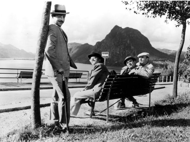 Drei Männer sitzen an auf einer Bank am Ufer eines Sees und blicken zu einem vierten Mann, der an einem Baum lehnt.