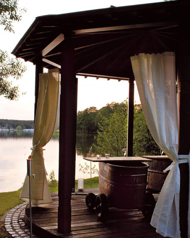 Ein Pavillon mit Holzbadewannen am See.