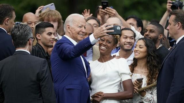 Joe Biden knipst Selfies mit Teilnehmenden des Grillfests.