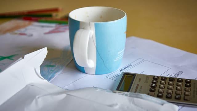 Kaffeetasse, Rechner und Mahnung auf einem Tisch. (Symbolbild)