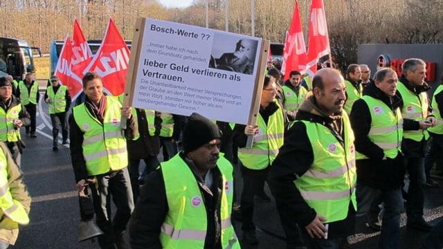 Demonstrierende Mitarbeiter in Leuchtwesten mit Transparenten und Fahnen.