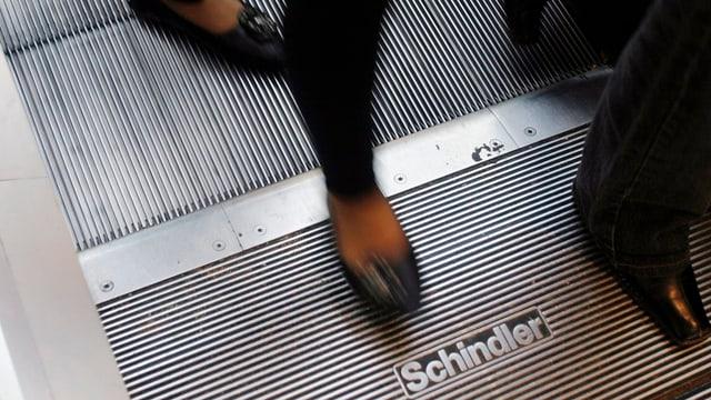 Nahaufnahme von Füssen einer Person, die eine Rolltreppe verlässt.