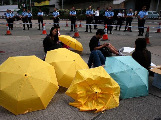 Drei Aktivistinnen sitzen hinter Regenschirmen auf der Strasse und werden von einer Polizeieinheit hinter einer Abschrankung beobachtet.