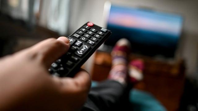 Eine Hand zeigt mit der Fernbedienung auf einen Fernseher.