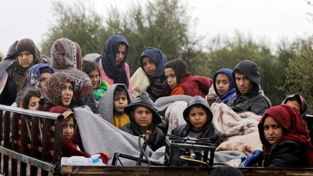 Frauen und Kinder auf einem Wagen zusammengepfercht.