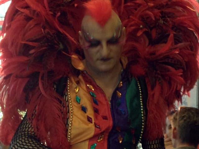 Mann mit aufgestellten Federn am Kostüm, stark Geschminkt.