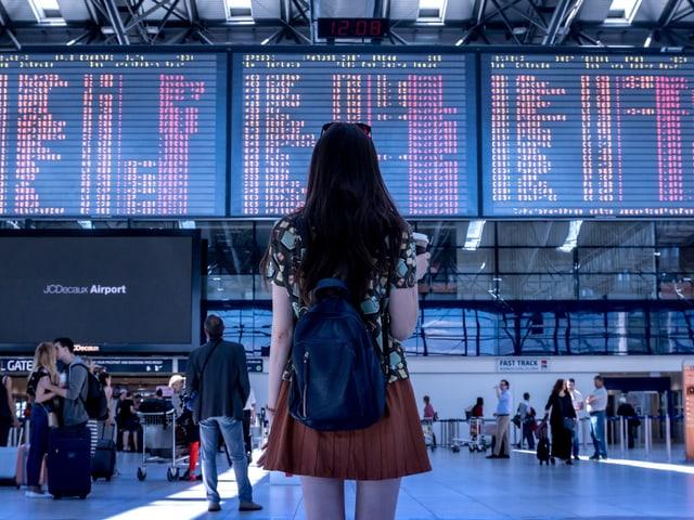 Mädchen steht vor der Abflugtafel am Flughafen
