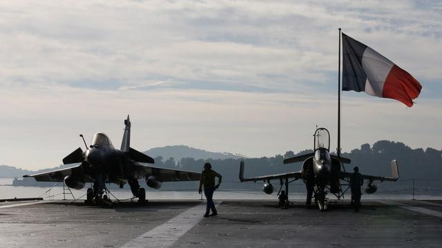 Zwei Kampfjets vor einer französischen Flagge.