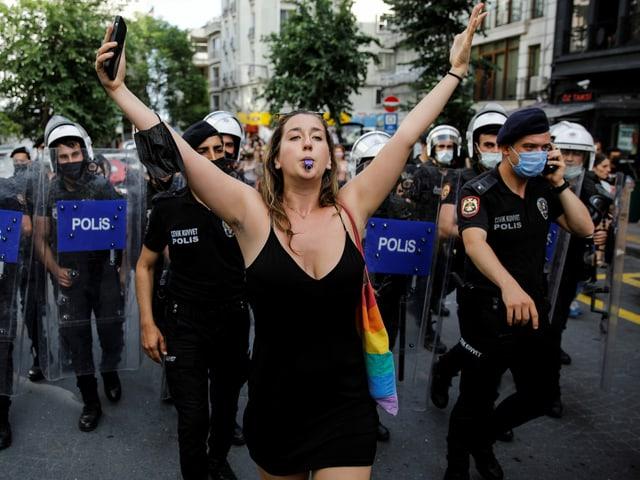 Eine Demonstrantin mit Regenbogentasche breitet die Arme aus und pfeift mit einer Trillerpfeife, hinter ihr Polizei