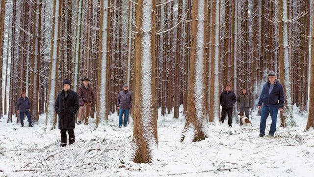 Männer stehen in einem verschneiten Wald.