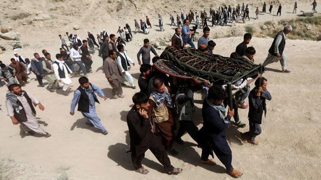 Männer tragen einen Verstorbenen zum Grab, Dutzende weitere Männer folgen der Prozession.