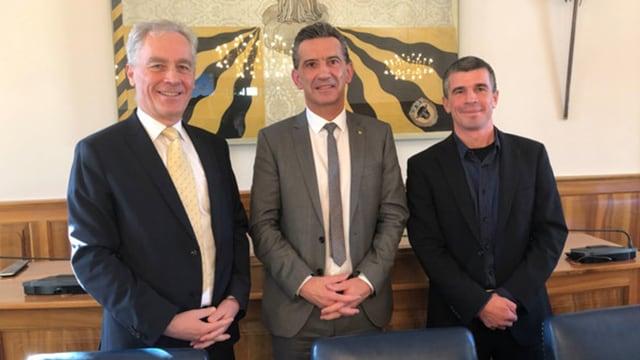 Drei Männer in dunklen Anzügen stehen vor einer Wand dahinter ein Teil eines Bildes.