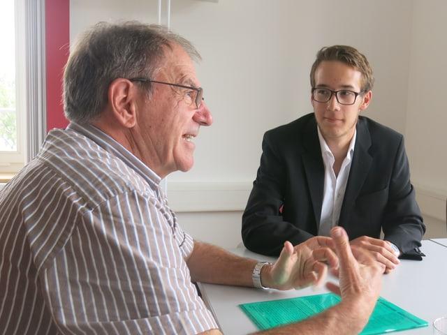 Zwei Herren diskutieren an einem Tisch.