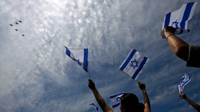 Menschen schauen eine Flugshow der Luftwaffe an und halten israelische Flaggen hoch.