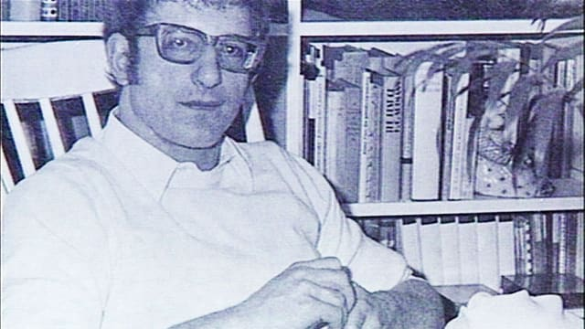 Portrait von Fritz Mars vor seinem Bücherregal.
