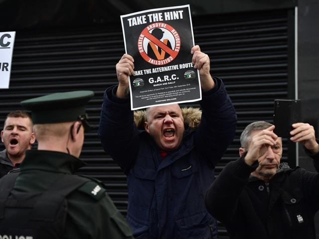 Anwohner demonstrieren gegen den Umzug mit Schildern und Plakaten. Ein Polizist überwacht die Situation.
