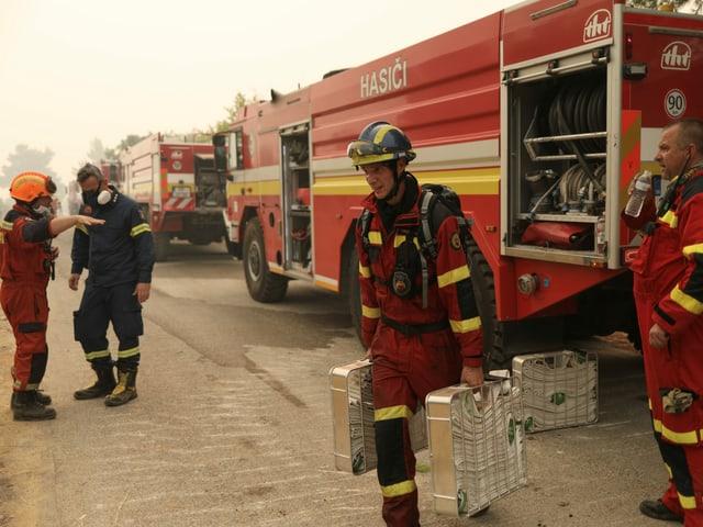 Feuerwehrmänner stehen um ein Fahrzeug herum. Ein Mann lädt Feuerwehrschläuche ab.