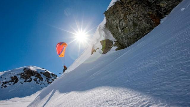 Ein Speedflyer mit Gleitschirm an einem verschneiten Hang.