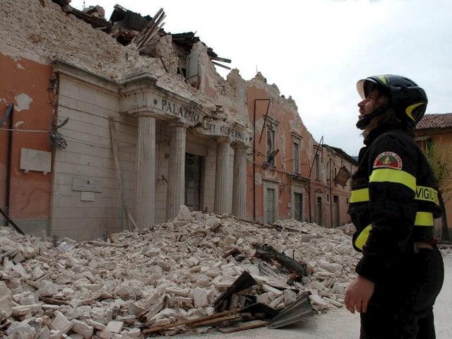Ein Feuerwehrmann steht vor einem stark beschädigten Palazzo.