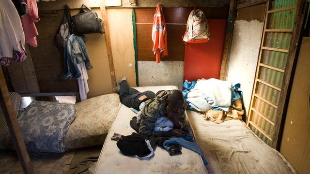 Ein afrikanischer Mann auf einer Matratze in einer baufälligen Hütte