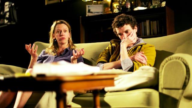 Ein Mann und eine Frau sitzen auf einem Sofa.
