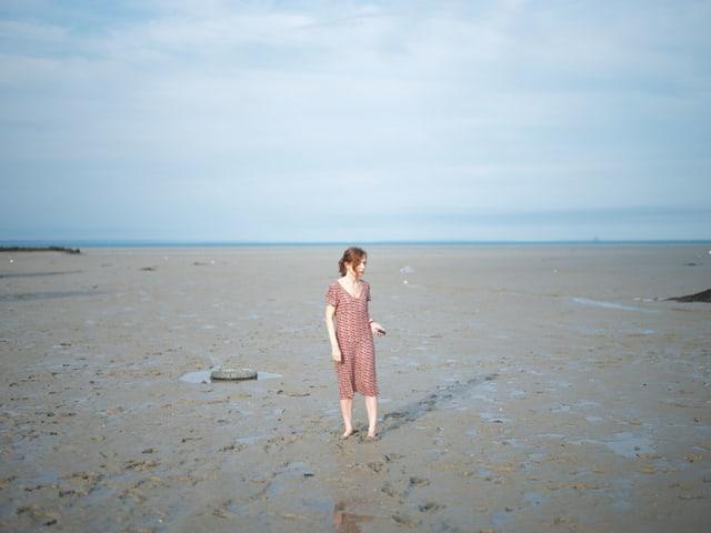 Eine Frau steht barfuss am Strand und schaut wirr umher.