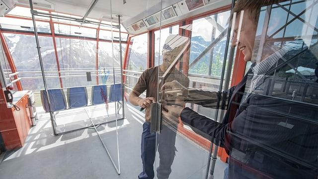 Zwei Männer montieren in der Gondel Plexiglasscheiben.