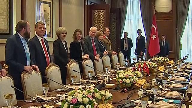 Britische Delegation mit Theresa May stehen am Sitzungtisch.