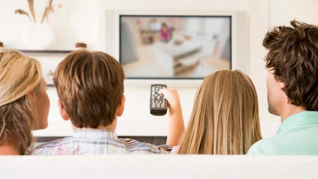 Eine Familie auf dem Sofa am Fernsehen