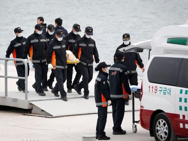 Ein Team in Uniform und mit Schutzmasken trägt eine Bahre mit einer Leiche in einer weissen Hülle zu einer Ambulanz.