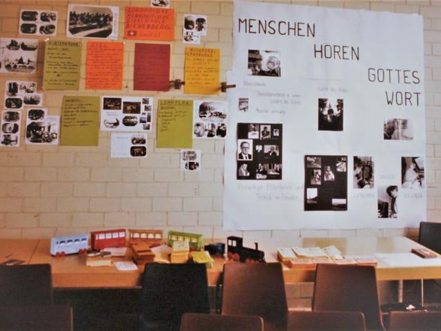 """Man sieht eine Backsteinwand, vor welcher zwei Tische angeordnet sind. An der Backsteinwand hängen viele farbige Plakate und Bilder. Neben den farbigen Plakaten hängt ein grosses Bild mit der Aufschrift """"Menschen hören Gottes Wort""""."""