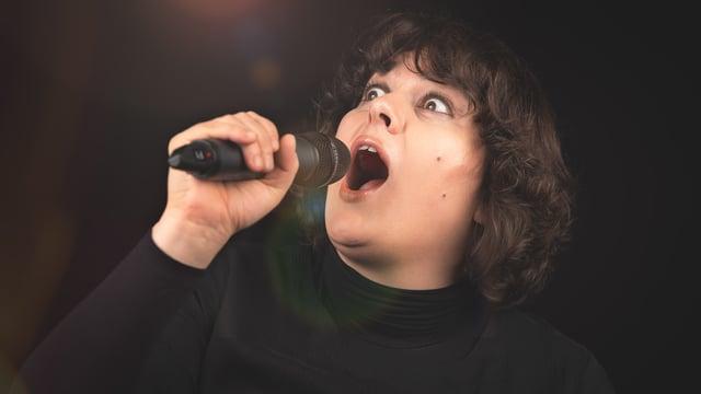 Eine Frau mit aufgerissenen Augen und Mikrophon in der Hand.