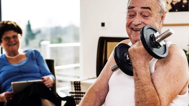 Senior stemmt zu Hause lächelnd eine Hantel. Seine Frau schaut ebenfalls lächelnd zu.
