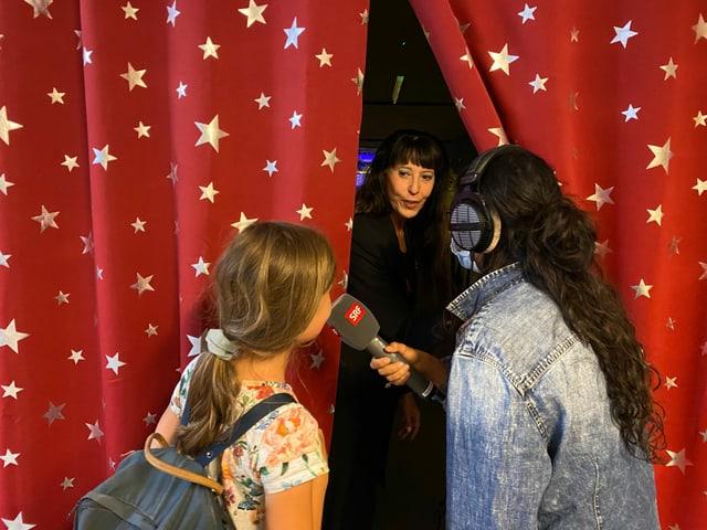 Julia und Rosa-Malena stehen vor dem Vorhang.