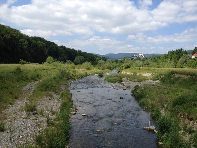 Flüsschen mit Kies und Gras an den Ufern. Im Hintergrund ein Schloss.