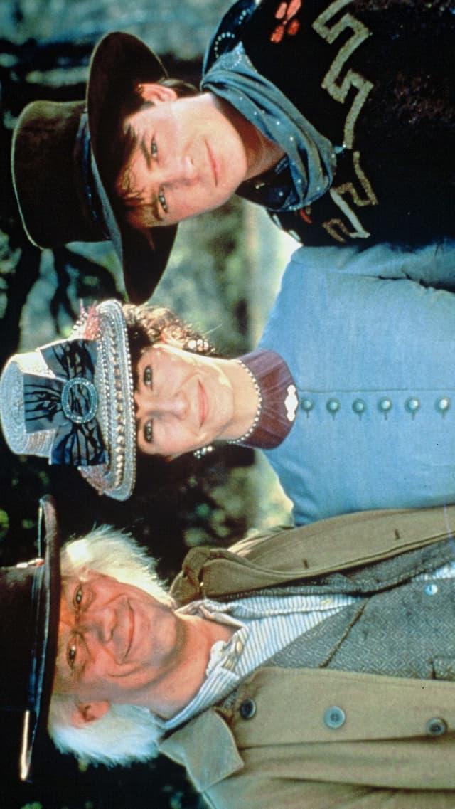 Ein älterer und ein jüngerer Mann und eine Frau in Wild-West-Kleidung.
