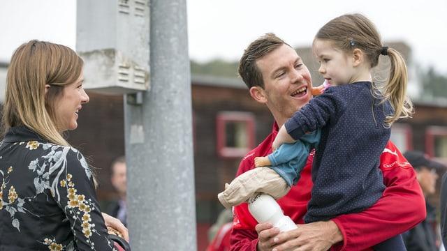 Stephan Lichtsteiner mit seiner Tochter auf dem Arm. Fau Manuela steht daneben.