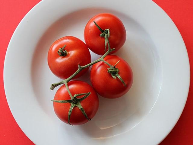 Vier Tomaten auf einem Teller.