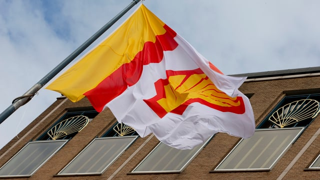 Bandiera cun il logo da la Royal Dutch Shell avant la sedia a Den Haag en l'Ollanda.