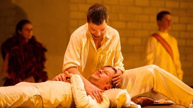 Ein Mann sitzt im Schneidersitz, ein anderer legt ihm den Kopf in den Schoss.