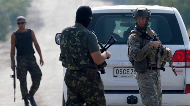 Ukrainische Soldaten vor einem Wagen der OSZE-Mission in der Ukraine