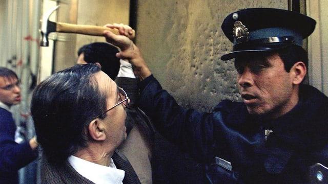 Mann mit Hammer und ein Polizist