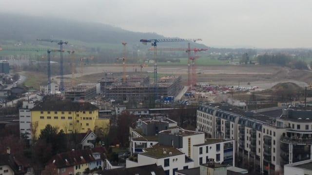 Vorne die Stadt, in der Mitte die Baustelle, und dahinter die brauen Fläche, wo später der Rest des Stadtquartiers enstehen soll.