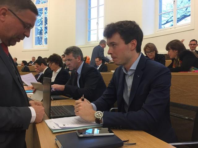 Adrian Schoop sitzt im Parlament und spricht mit einem Mann