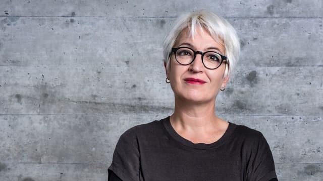 Eine Frau mit weissem Haar und dunkler Brille.
