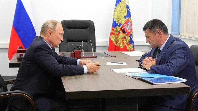 Wladimir Putin und Andrei Tarasenko sitzen sich an einem Tisch gegenüber.