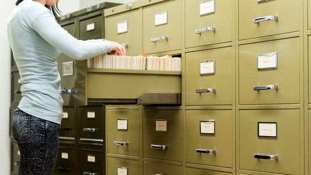 Eine Frau vor einem Schrank mit vielen Dossier.