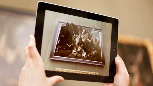 Ein Gemälde auf einem Tablet. Die Figuren des Gemäldes ragen aus dem Gemälde.